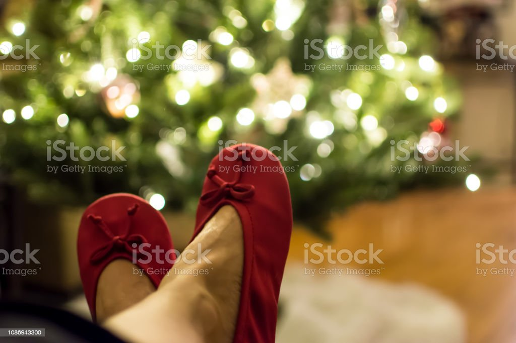 Woman wearing red slippers with legs up relaxing and illuminated Christmas tree lights in background stock photo