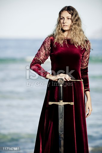 portrait of medieval lady in flashy satin dress guarding the kings sword for novel concepts,selective focus, creative dramatic color retouching to underline the ancient medieval time,vignetting