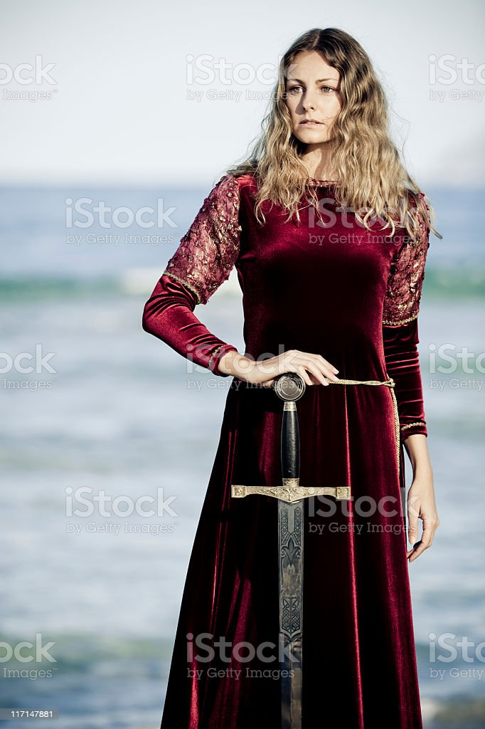 Woman wearing red velvet medieval gown holding a sword stock photo