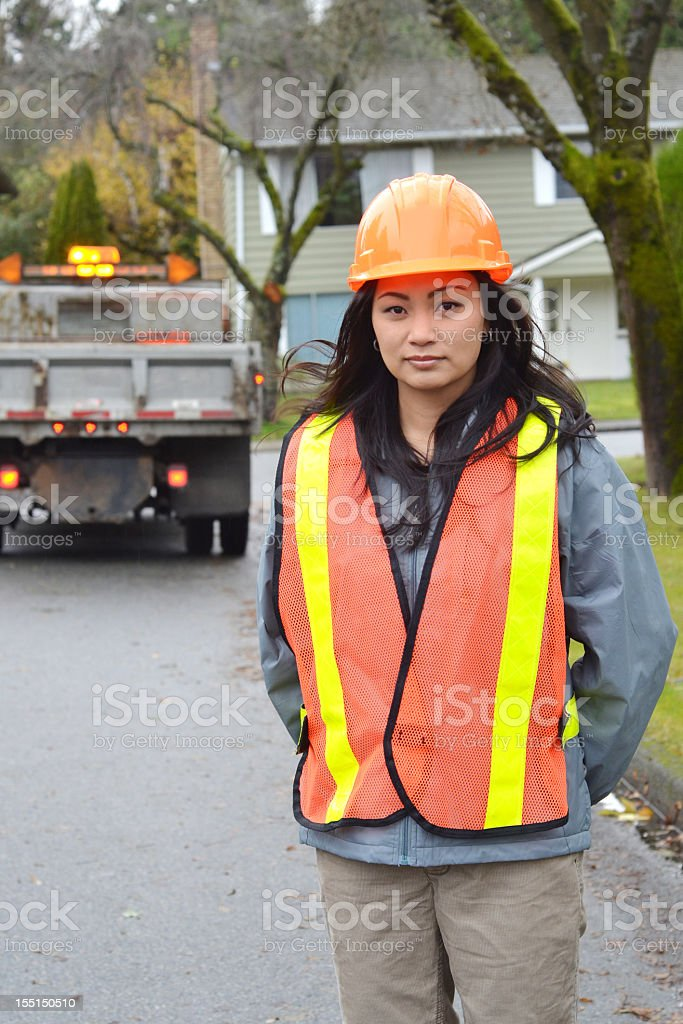 Woman wearing safety gear with truck in the background royalty-free stock photo