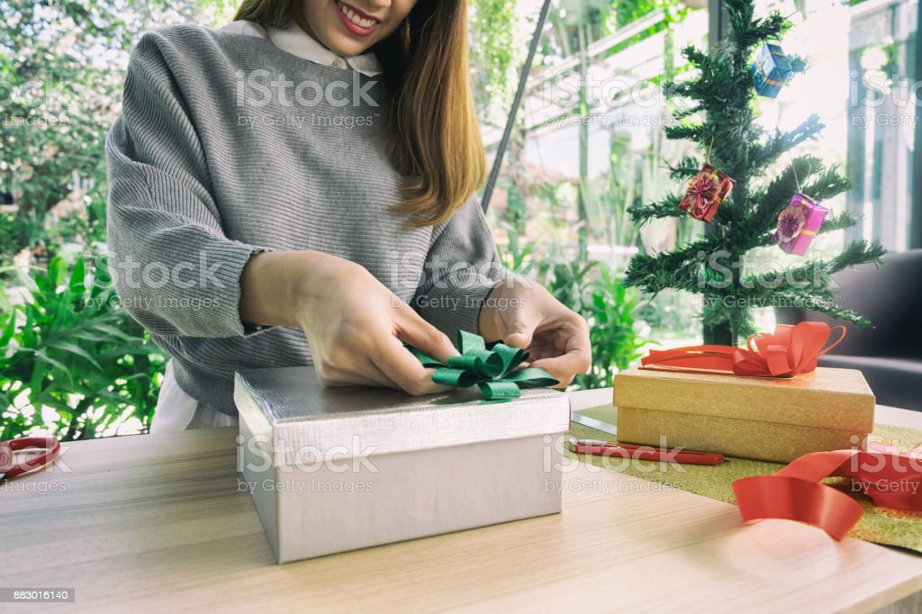 woman wearing santa hat packaging gift box, christmas concept