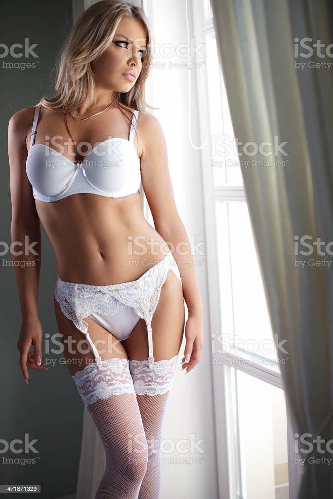 Woman wearing sexy lingerie standing in bedroom looking out window stock photo