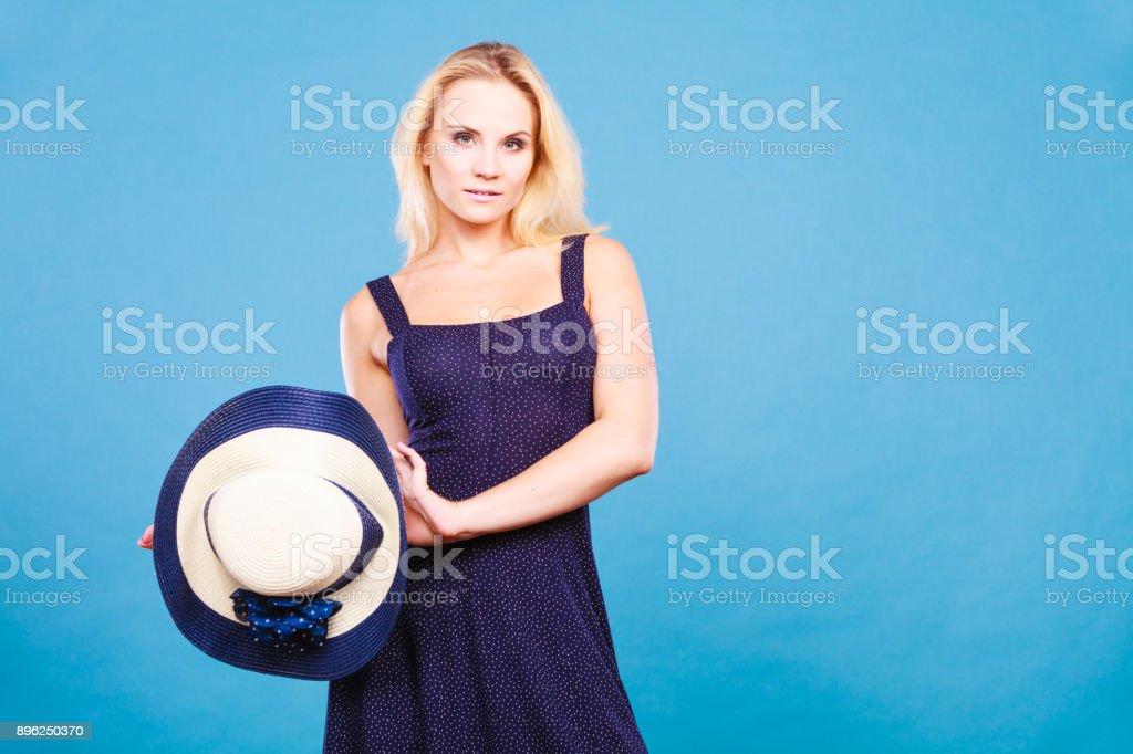 Mulher de vestido curto da Marinha segurando o chapéu de sol - foto de acervo