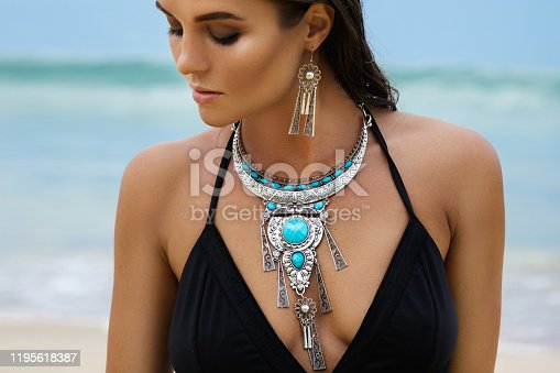 Beautiful and sexy woman on the beach wearing silver jewelry