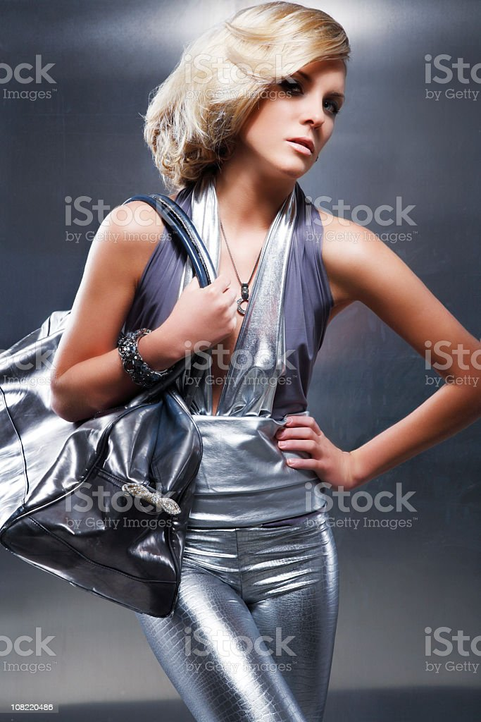 Woman Wearing Silver Outfit and Carrying Purse Posing royalty-free stock photo