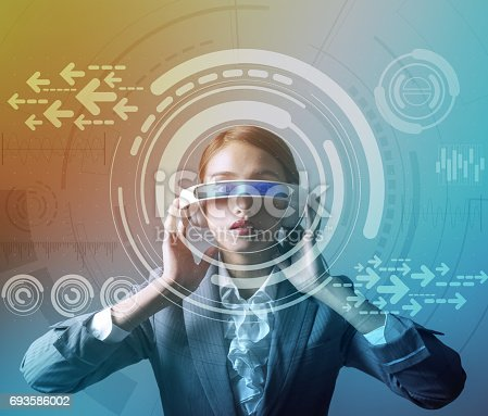 693586040istockphoto woman wearing smart glasses and futuristic graphical user interface 693586002