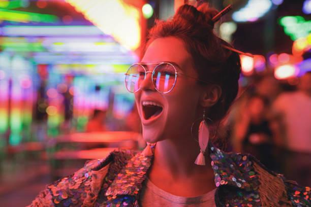 kobieta ubrana w musującą kurtkę na ulicy miejskiej z neonowymi światłami - jaskrawy kolor zdjęcia i obrazy z banku zdjęć