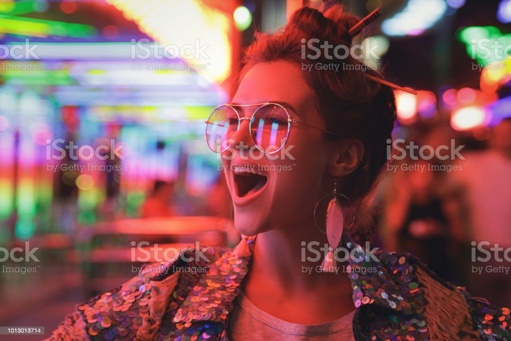Mulher vestindo jaqueta espumante na rua com luzes de néon da cidade - foto de acervo