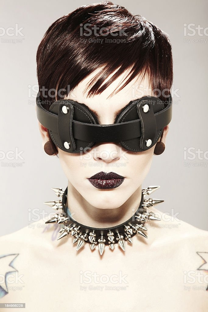 Woman Wearing Spiked Collar and Mask stock photo