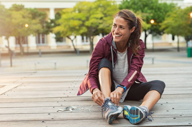 Woman wearing sport shoes Mature fitness woman tie shoelaces on road. Cheerful runner sitting on floor on city streets with mobile and earphones wearing sport shoes. Active latin woman tying shoe lace before running. exercising stock pictures, royalty-free photos & images
