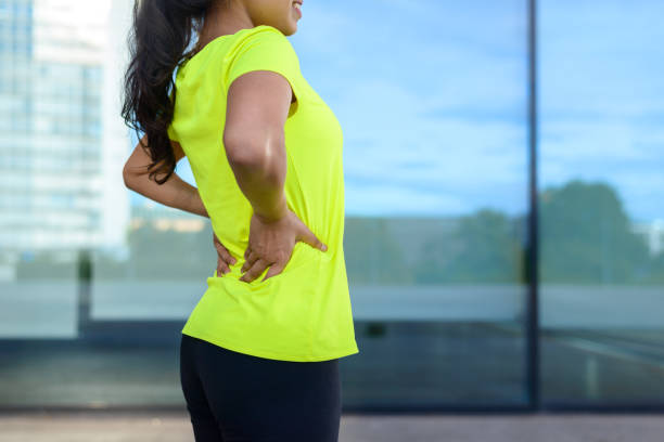 woman wearing sportswear holding painful back - low section stock photos and pictures