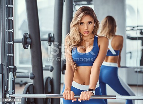 Beautiful girl wearing sportswear is posing next smith machine in the fitness center.