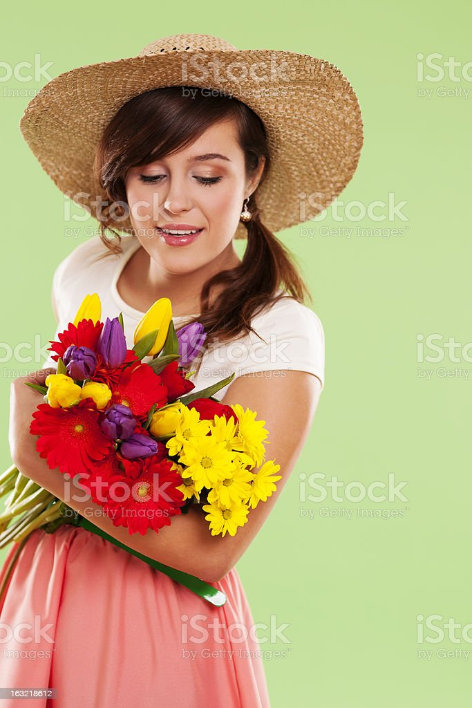 Woman wearing straw hat holding spring flower royalty-free stock photo