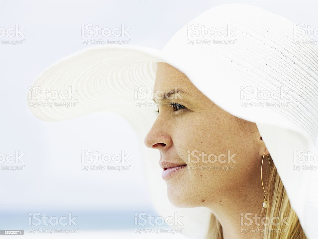 Woman wearing sunhat looking out ocean behind Lizenzfreies stock-foto