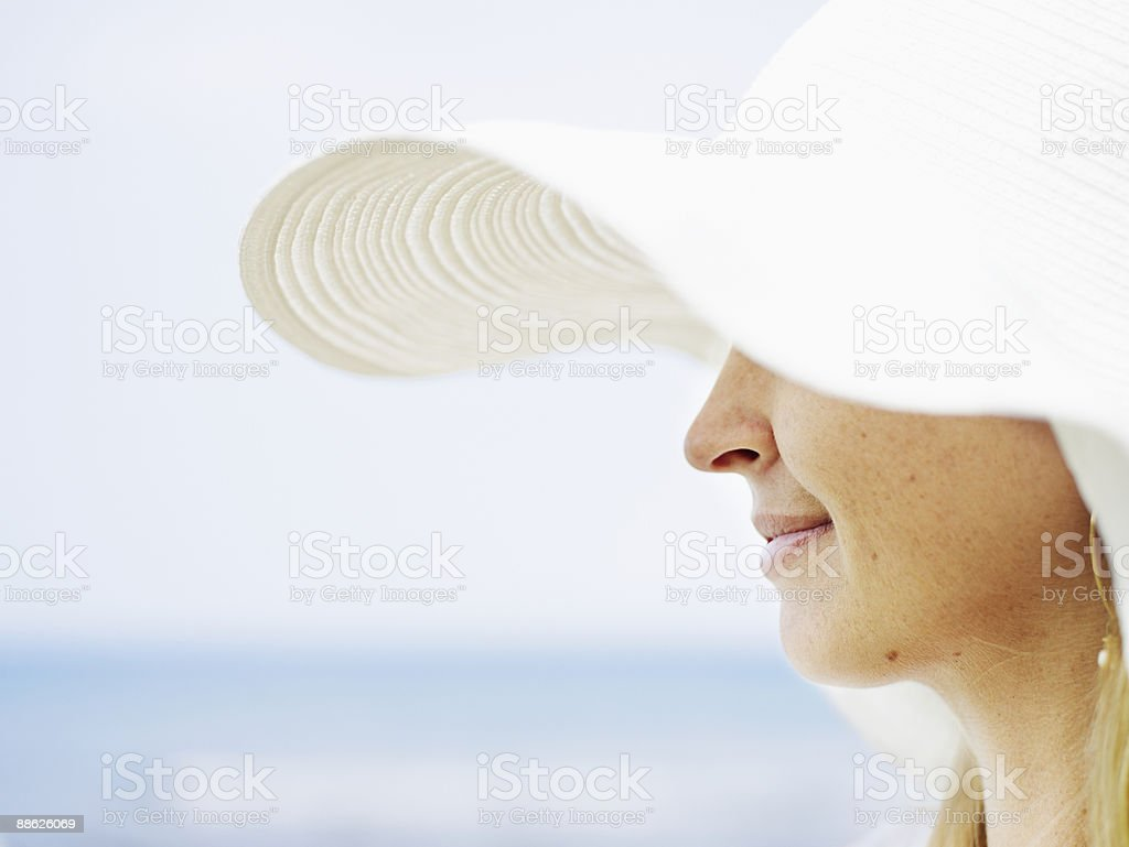 Woman wearing sunhat smiling ocean in background 免版稅 stock photo