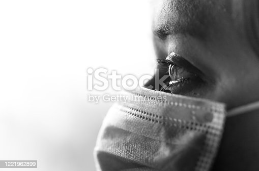 Close up black and white image depicting a caucasian woman, in her 30s with brown hair, wearing a blue surgical face mask for safety and protection during the coronavirus (Covid-19) pandemic. The woman has intense brown eyes which are in sharp focus. Room for copy space.