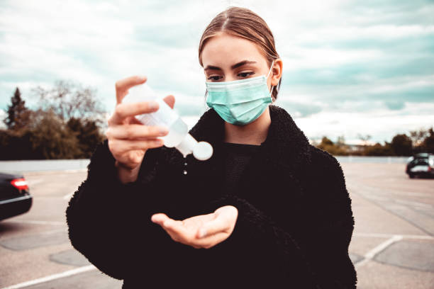 Woman Wearing Surgical Mask Disinfecting Hands Corona Covid-19 Series stock photo