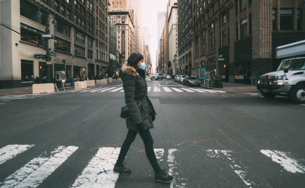 マンハッタンのミッドタウン、ニューヨークの横断歩道を通る外科用マスクを着用した女性 - corona newyork ストックフォトと画像