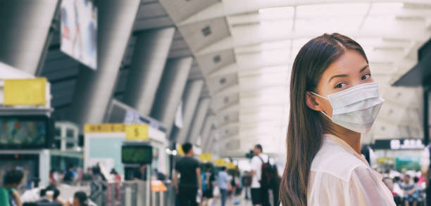 Woman wearing surgical mask in train or bus station walking indoors. Prevention in public spaces stock photo