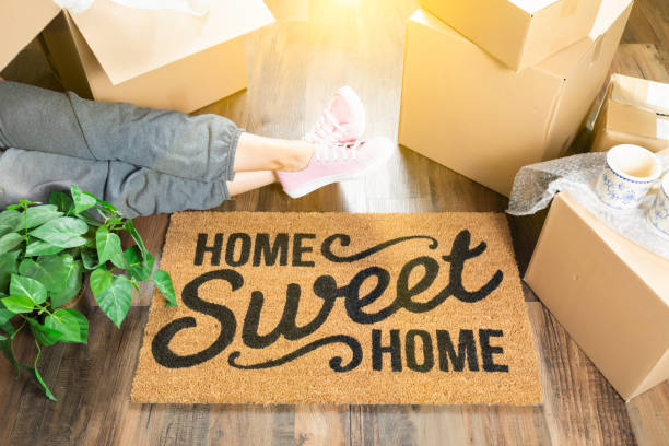 woman wearing sweats relaxing near home sweet home welcome mat, moving boxes and plant. - house hunting stock photos and pictures