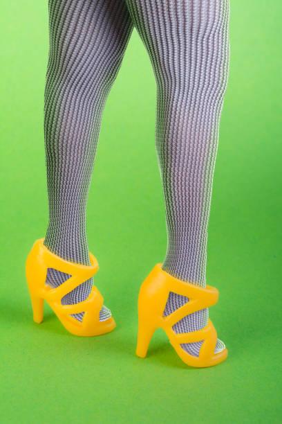 frau trägt spielzeug gelb kunststoff-sandalen - barbiekleidung stock-fotos und bilder