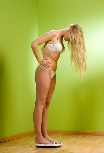 Woman Wearing Underwear and Checking Weight stock photo