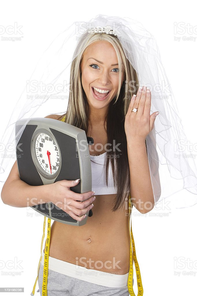 Woman wearing veil and engagement ring holding scales royalty-free stock photo