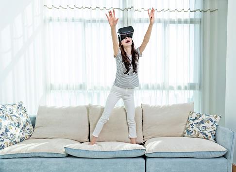 Woman wearing virtual reality simulator at home