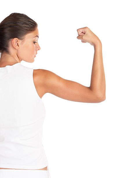 A woman wearing white flexing her arm stock photo