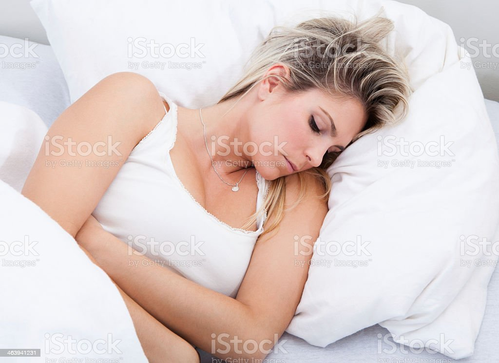A woman wearing white in bed experiencing stomach pains stock photo