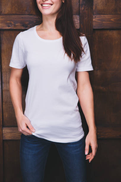 Woman wearing white t-shirt in front of wooden wall stock photo