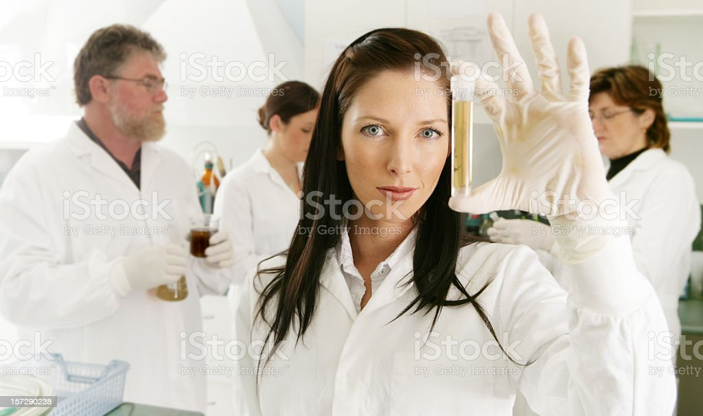 Woman wearing white with latex glove holding vile in lab royalty-free stock photo