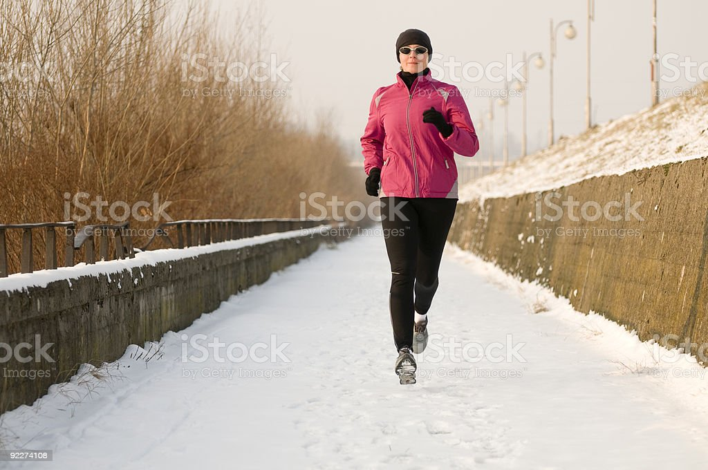 Woman wearing winter gear running down a snowy path royalty-free stock photo