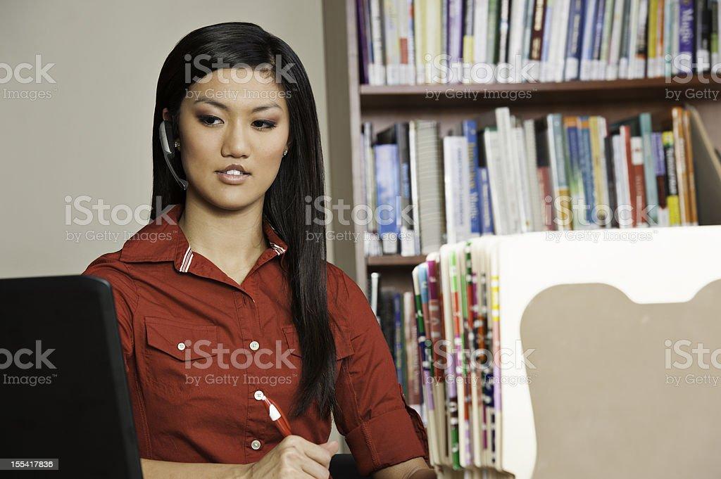 Woman wearing wireless earpiece in medical office royalty-free stock photo