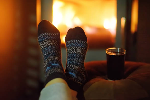 Woman wearing woollen socks near Christmas fireplace Woman wearing woollen socks near fireplace. Christmas eve concept. Winter holidays - Xmas and New Year. Cozy evening in the cold weather log fire stock pictures, royalty-free photos & images