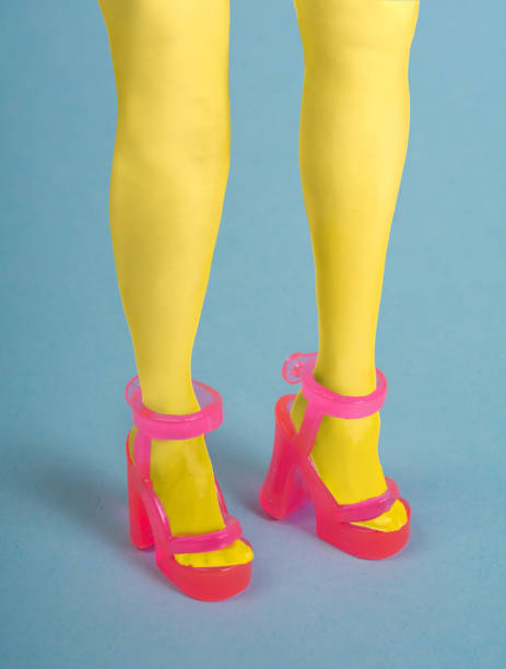 Woman wearing yellow tights and pink transparent toy plastic sandals stock photo