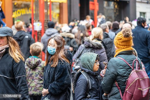 1202557009istockphoto A woman wears a protective face mask in London on a rainy day. Selective Focus. Concept of coronavirus quarantine. 1209646919