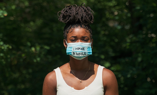 A young woman wears a face mask during global pandemic that says