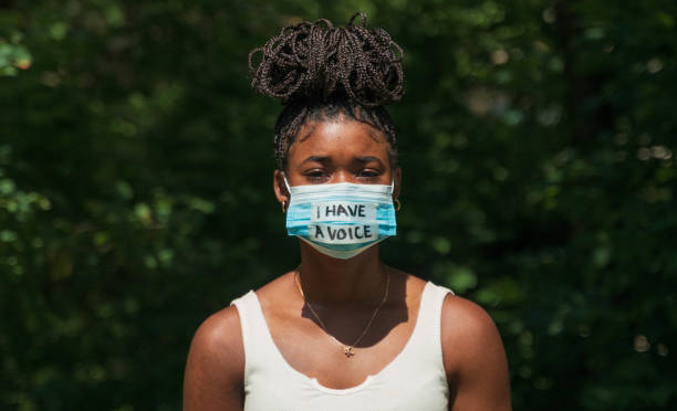 Woman wears face mask with protest message stock photo