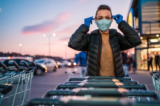 Eine Frau trägt medizinische Schutzhandschuhe und eine Maske beim Einkaufen von Lebensmitteln. – Foto