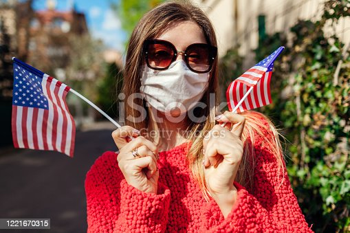 istock Woman wears protective mask outdoors celebrates USA Independence day holds flags during coronavirus covid-19 pandemic. 1221670315