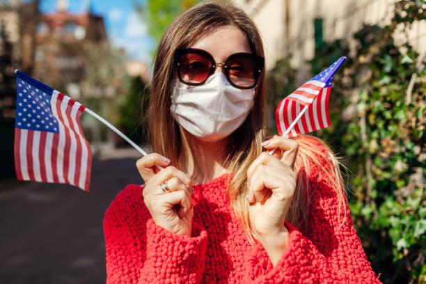 woman wears protective mask outdoors celebrates usa independence day holds flags during coronavirus covid-19 pandemic. - fourth of july zdjęcia i obrazy z banku zdjęć