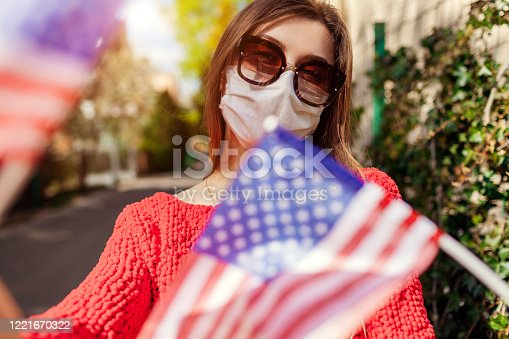 istock Woman wears protective mask outdoors celebrates USA Independence day holds flags during coronavirus covid-19 pandemic. 1221670322