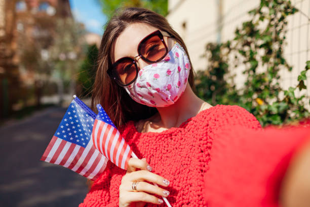 Woman wears protective mask outdoors celebrates USA Independence day holds flags during coronavirus covid-19 pandemic. stock photo