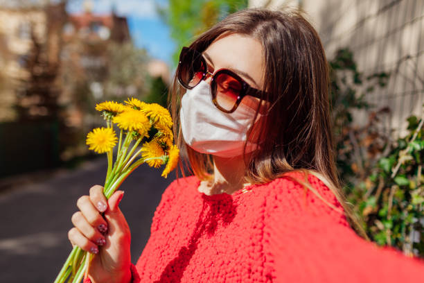 Woman wears protective mask outdoors during coronavirus covid-19 pandemic on empty street smells flowers.