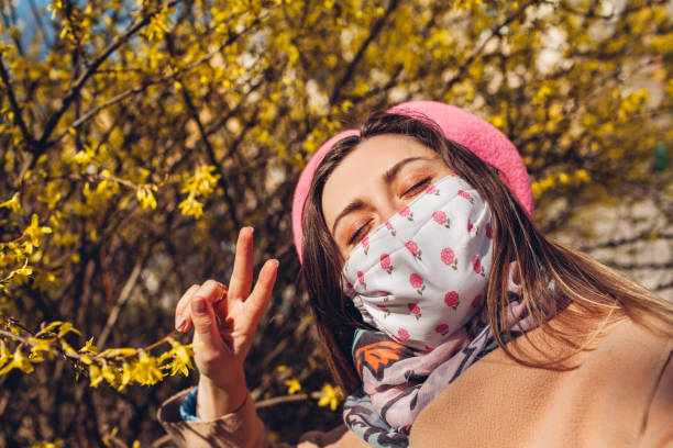 Woman wears reusable mask outdoors during coronavirus covid-19 pandemic. Girl takes selfie with flowers. Stay safe