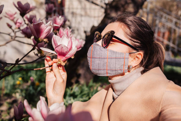 Woman wears reusable mask outdoors during coronavirus covid-19 pandemic. Girl smells magnolia flowers. Stay safe