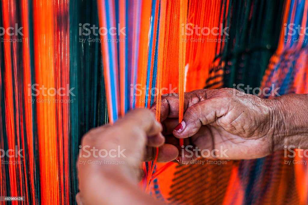 Woman weaving a Wayuu hammock (chinchorro). stock photo