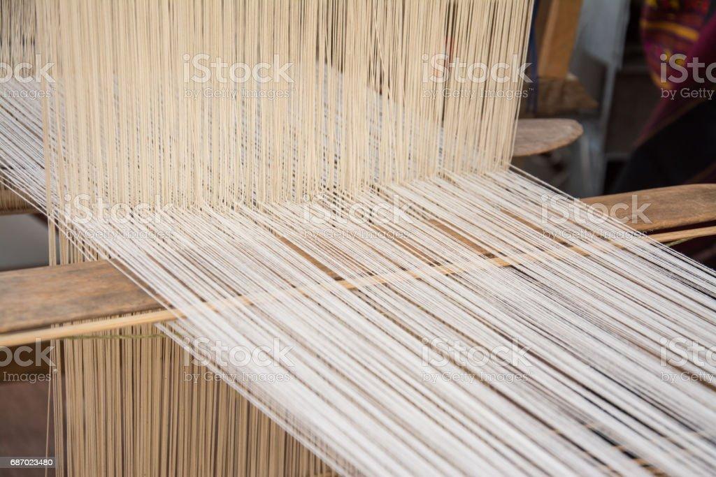 Woman weaving silk in traditional way at manual loom. Thailand stock photo