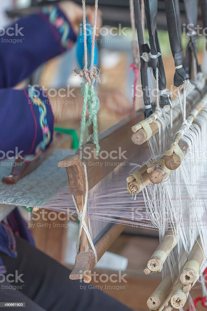 Woman weaving white pattern on loom stock photo